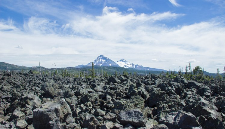 The view of the Three Sisters behind the vastness of lava rock